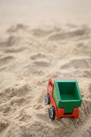 砂の大きいタイヤ印刷背景におもちゃのトラック 写真素材