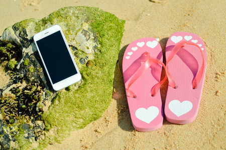 Flipflops and mobile phone on sandy ocean beach vacation of concept, flat lay style top view Stock Photo