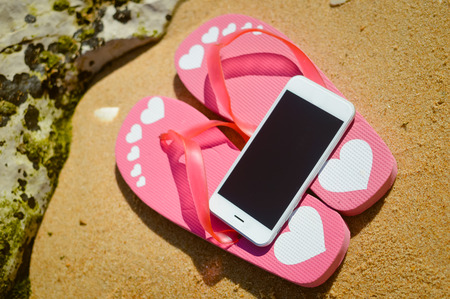 Summer beach with smart phone on sandy outdoors background
