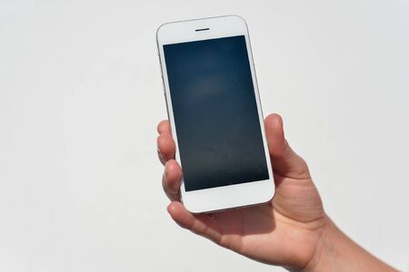 self discovery: Hand holding smart mobile phone on light wall background, closeup picture