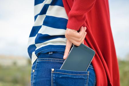 persons back: Primer en la mano de la mujer lleva a cabo teléfono inteligente de su bolsillo trasero de los pantalones vaqueros en el fondo al aire libre
