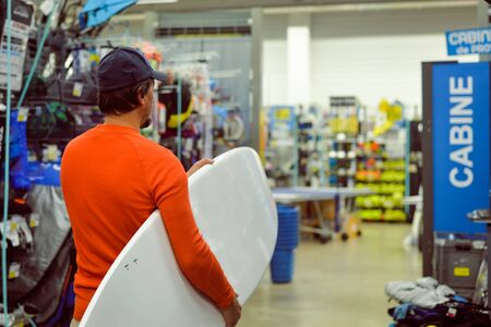 surf shop: Back view of man holding a white surf board on shop indoor background