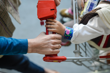 shopping trip: Mother and child on shopping trip. Closeup on woman with mobile phone and store cart holding by hand Stock Photo