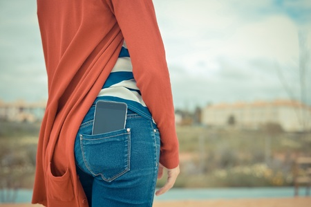 Closeup on smartphone in the back pocket of a womans jeans, blank screen with clipping path for you to add your own message or design
