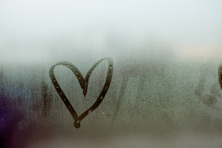 tarnished: Sign of love heart on glass. The window is fogged up background texture