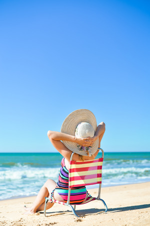 Rear view of woman in chair on summer time sun light beach holiday location. Blue sunny background Stock Photo