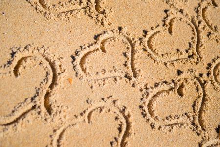suelo arenoso: Grupo de los muchos símbolos de amor del corazón en el fondo de sol playa de arena. saludos desde las vacaciones encantadora vacaciones. Foto de archivo
