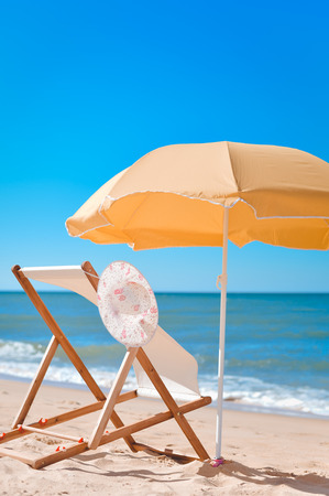longue: Sun parasol, chair longue and female hat on vacation beach sun shine outdoors