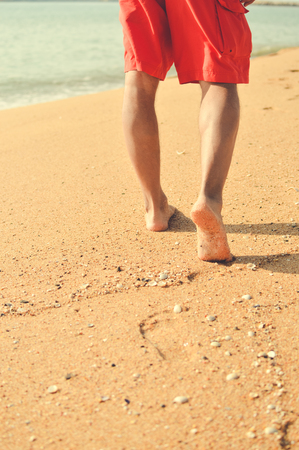 short wave: Man walking or running on the sunny beach sandy background Stock Photo