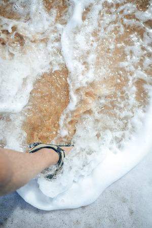 ankle strap: Leg in sandals in the foam water, closeup top view