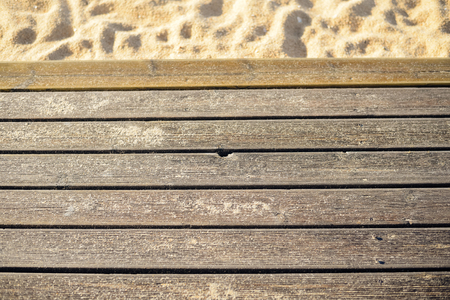 Sunny summer day with wooden walkway on sandy beach background Фото со стока