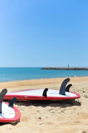 surfboard fin: Surfboards lying on sand ocean beach background, closeup outside Stock Photo