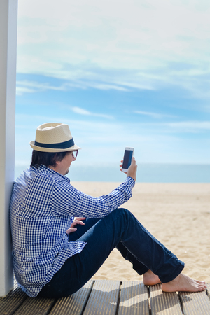 barefoot man: Handsome man sitting using mobile smartphone, seaside background. back side view of barefoot man on blue sky outside terrace