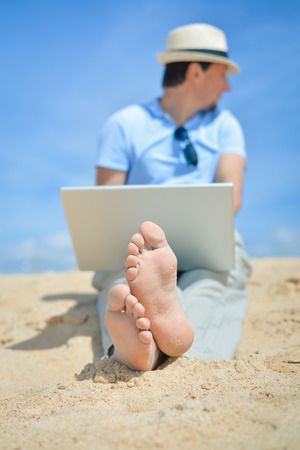 Happy business man in hat working using notebook computer on the beach blue sky background outside. Stock Photo