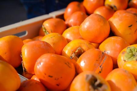 Closeup on orange persimmon kaki fruits freshly collected at the market boxes Stock Photo