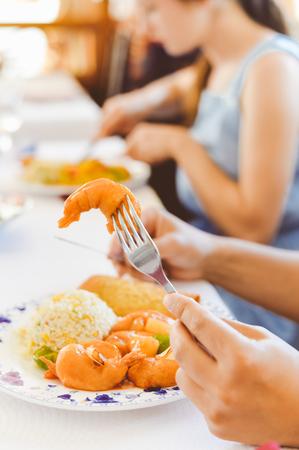 海の食べ物と手のオリエンタル ライスをフォーク ナイフすぐ写真を保持します。