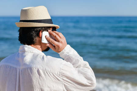 roaming: Back view closeup of person talking on cell phone walking by open water blue sky horizon, sunlight outdoors background. Stock Photo