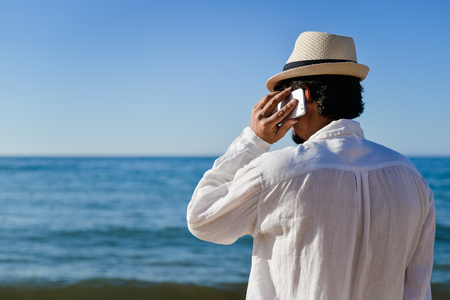 roaming: Back side view of man talking on smart phone, vacation beach background Stock Photo