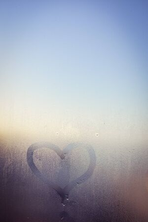 tarnished: Love heart painted on glass. The window is fogged up with drops on the background, closeup