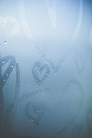 part of me: Primer en símbolos del corazón del amor borrosa abstractas dibujadas a mano en el fondo de la luz solar cristal de la ventana congelada húmeda. enfoque selectivo utilizado. Foto de archivo