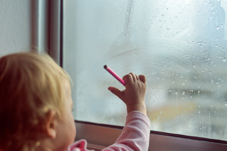picture window: A child with pencil drawing picture on fogged or frozen window glass, close up