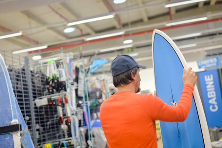surf shop: Man holding in hands and choosing surf board on shop background indoors