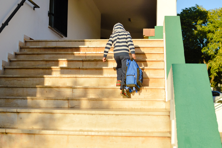 Back view of boy walking on stairs outdoors building background