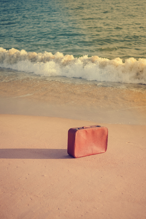 parting the sea: Retro suitcase, open water and sandy beach outdoors background Stock Photo