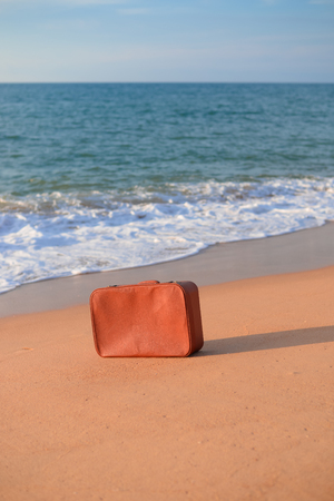 parting the sea: Lonely suitcase on vacation. Concept of travel to sea beach outdoors background Stock Photo