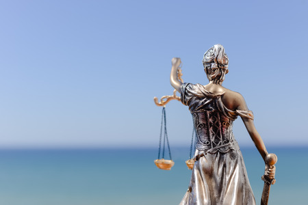 Back view of Justice Themis goddess sculpture on bright sky copy space background.