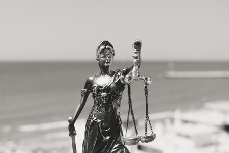 Justice Themis goddess sculpture on bright sky copy space background. Black and white image