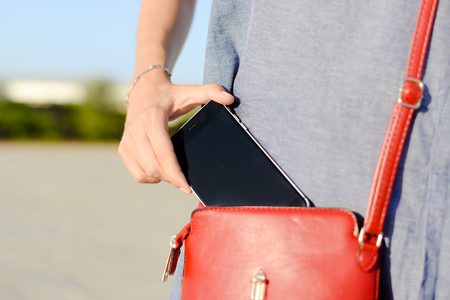 Closeup photo of stylish female taking cellphone out of handbag, sunny outdoors background Stock fotó