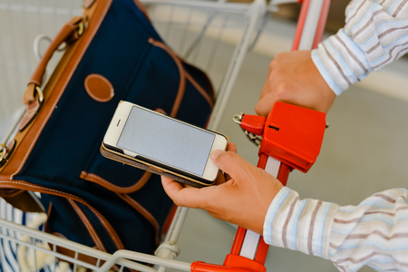 Top view closeup on person shopping online using mobile phone, trolley mall. Light smartphone mock up background