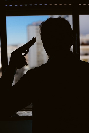 holding gun to head: Silhouette of a man holding a gun at the head, window background Stock Photo