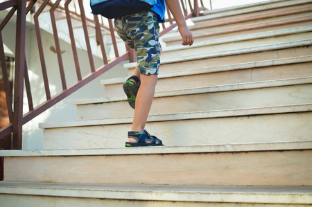Back view of school boy carrying rucksack bag climbing up on the stairs background. Stock Photo