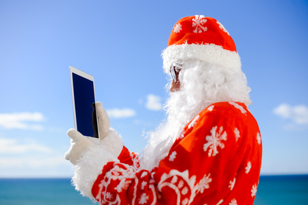 Santa Claus holding choosing receivers of gifts on tablet computer on sunny day blue sky outdoors background. Back side view closeup image Stock Photo