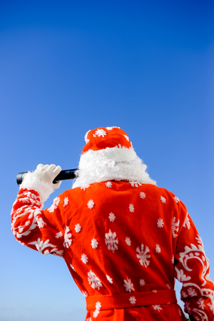 spying: Santa Claus looking through telescope on sunny blue sky outdoors background. Closeup back side view image Stock Photo