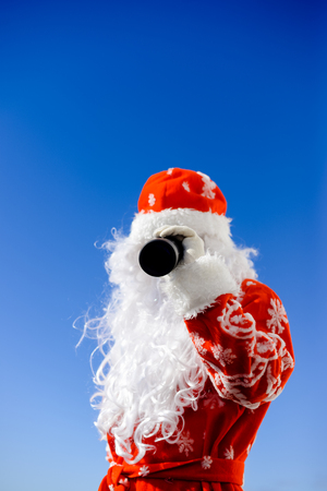 Santa Claus looking through telescope on sunny blue sky outdoors background. Closeup back side view image Reklamní fotografie