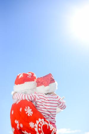 saint nicolas: Back view of little kid hugging Santa Slaus over blue sky outdoors background