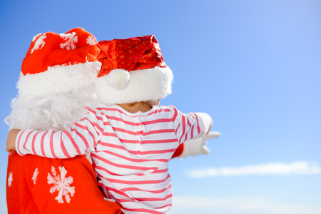 saint nicolas: Back view of joyful excited little kid hugging Santa Claus over blue sky outdoors background