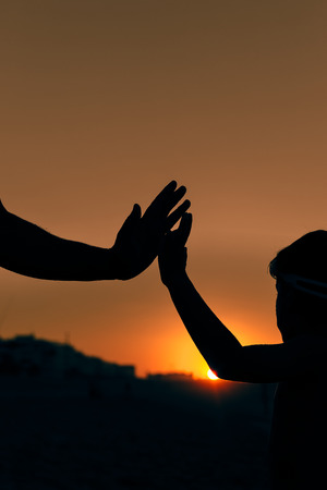 Closeup view of child and adult hands on sunset outdoors background. Stock Photo