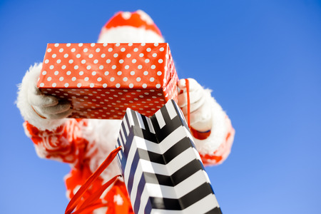 ship with gift: Merry Christmas with joyful Santa Claus ready to ship and delivering gift packages on sunny blue sky outdoors background. Happy time for amazement and excitement Stock Photo