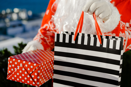Merry Christmas with joyful Santa Claus ready to ship and delivering gift packages on sunny blue sky outdoors background. Happy time for amazement and excitement Stock Photo