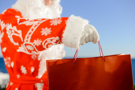 Merry Christmas with joyful Santa Claus ready to ship and delivering gift shopping bag on sunny blue sky outdoors background. Happy time for amazement and excitement