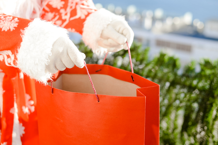 ship with gift: Merry Christmas with joyful Santa Claus ready to ship and delivering gift shopping bag on sunny blue sky outdoors background. Happy time for amazement and excitement