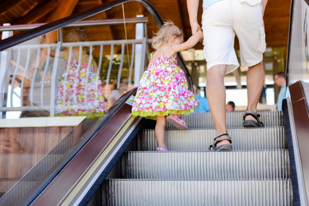 view of a staircase in a shop: Back view of caring father walking daughter on escalator stairs background