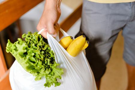 Hombre bolso que lleva en la mano después de las compras. Primer de la bolsa llena de frutas y verduras. Foto de archivo