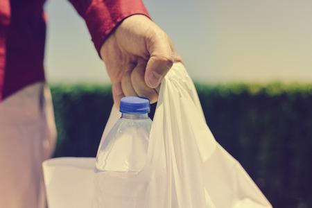 若い女性忙しい街の通りを歩いて、様々 な食料品と色のプラスチック買い物袋を保持している都市生活の高コスト 写真素材