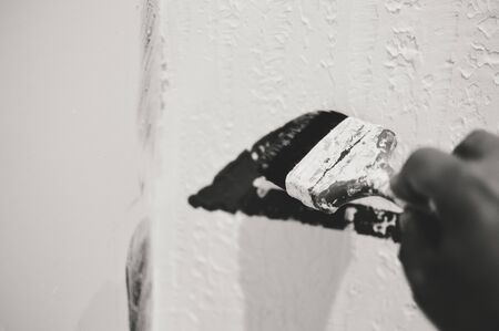 painting and decorating: Black and white closeup on hand painting decorating using paint brush