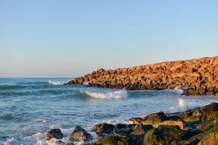 Sea waves over the breakwater rocks background at sunrise or sunset light Stock Photo